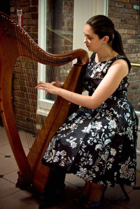 Alice shows great focus while honing her harp playing skills at an event. Courtesy of Alice Smyth